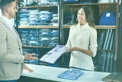 Woman seller assisting man in choosing shirt in men's cloths s Stock Photography