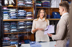 Woman seller assisting man in choosing shirt in men's cloths s. Young happy  women seller assisting men in choosing shirt in men's cloths store Royalty Free Stock Photography