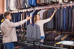 Woman seller assisting man in choosing suit in men's cloths st. Young cheerful positive women seller assisting men in choosing suit in men's cloths store Royalty Free Stock Images