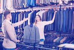 Woman seller assisting man in choosing suit in men's cloths st. Young women seller assisting men in choosing suit in men's cloths store Royalty Free Stock Images