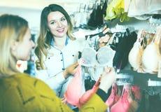 Woman seller assisting woman in choosing bra. Positive young women seller assisting women in choosing bra in underwear store Stock Images