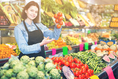 Woman seller helping customer to buy vegetables. Woman seller helping customer to buy fruit and vegetables in grocery shop stock photos