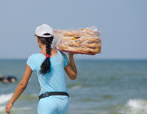 Woman - the seller, by the sea is a tray of baklava. Trade by the sea. The woman wears a tray of baklava Royalty Free Stock Images