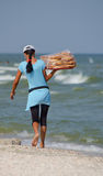 Woman - the seller, by the sea is a tray of baklava. Trade by the sea. The woman wears a tray of baklava Royalty Free Stock Photo