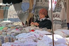 Woman seller sits and knits wool products for sale on the Market Square in the center of Vyborg stock image