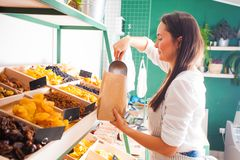 Woman seller take dry fruits from store counter royalty free stock image