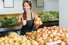 Woman seller wearing apron picking yellow onion bulbs Stock Image