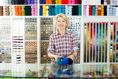 Woman seller with yarn balls. Mature smiling woman seller standing at counter with yarn balls in sewing store royalty free stock photography
