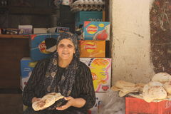 Woman selling bread in Kafr Ghataty. A woman selling bread in a rural area in Kafr Ghataty in Giza, in front of an old shop Royalty Free Stock Photography