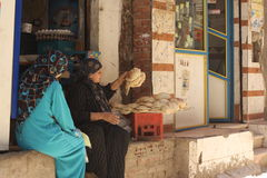 Women selling bread in Egypt. Women in traditional Egyptian dress sitting outside their shop selling unleavened bread or cobbers Stock Images