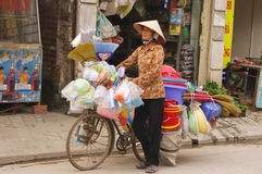 Woman selling brooms and plastic objects. This young woman is pushing his bike through the streets of Hanoi to sell brooms Rice straw or bamboo and plastic Stock Photography