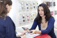 Woman selling a cell phone Stock Images