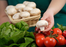 Woman selling champignon mushrooms Stock Images