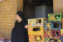Woman selling crisps. Old woman selling crisps in flea market of Kafr Ghataty, Egypt Royalty Free Stock Image