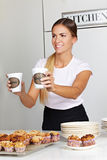 Woman selling coffee in café Stock Images