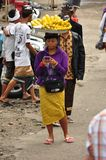 Woman selling corn cobs. Woman carrying on her head a tray with boiled corn cobs for sale. Photograph taken on Bali in Indonesia stock photography