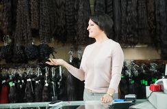 Woman selling different color hair extensions. Elegant woman selling at different color hair extensions in salon Royalty Free Stock Images