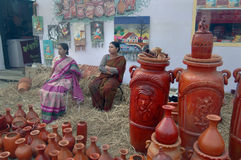 Woman selling in fair. Two Indian women have displayed pottery items for sell in a fair in urban India Royalty Free Stock Images