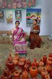 Woman selling in fair. Two Indian women have displayed pottery items for sell in a fair in urban India Stock Photos