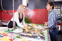 Woman selling fish to male customer in store. Mature women selling fish to male customer in store Stock Image