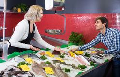 Woman selling fish to male. Mature women selling cooled fish to male customer in store Stock Photography