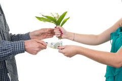 Woman selling flowers to a man, he gives her money Royalty Free Stock Image