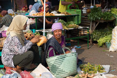 Woman selling fruit and vegetables in wet market near Borobudur temple, Java, Indonesia. Women sitting on the floor amidst the produce, talking and laughing in Stock Photos