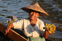 A woman selling fruits and flower from her small boat Royalty Free Stock Photo