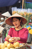 Woman selling fruits in a street market of Hoàn Kiếm, the old quarter of Hanoi Stock Image
