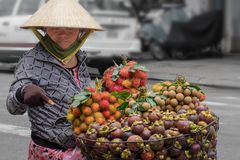 Saigon, Vietnam - June 30, 2017: Woman selling fruit on street, Saigon, Vietnam. Woman selling fruits and vegetables on street in Saigon Vietnam royalty free stock photography