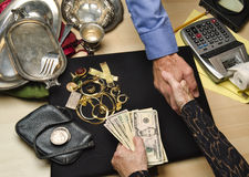 Woman selling gold and silver. Woman receiving cash for gold and silver items Stock Photography