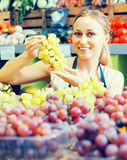 Woman selling grapes at market Stock Image
