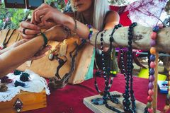 A woman selling homemade craft jewelry from a market stall. At a hippy festival stock photography