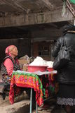 Woman selling kashk in Osh. An old woman in traditional dress selling kashk in the bazaar in Osh, kyrgyzstan. It's a diary product popular in central asia and Royalty Free Stock Image
