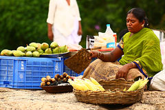 Woman selling mangoes and cooked corn. Indian woman selling mangoes and steamed corn on road side at a popular park (Lalbagh) at Bangalore, India Stock Photo