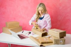 Woman selling merchandise online and packaging items for mail stock photography