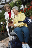 Woman Selling Plant To Disabled Woman At Botanical Garden. Senior Woman selling plant to a disabled women on motor scooter at botanical garden Royalty Free Stock Images