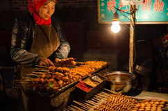 A woman selling roast gluten. In xi 'an street night market selling roasted the gluten women on both sides of the light Stock Images