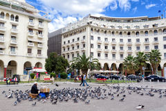 Woman selling seeds for feeding the pigeons in Famous square Ari Royalty Free Stock Photo