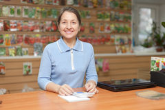 Woman selling seeds in store for gardeners. Friendly mature woman selling seeds in store for gardeners Royalty Free Stock Images
