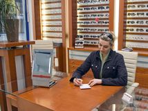 Woman selling spectacles. A woman working in an optician shop, sitting at the desk and writing something, lots of glasses behind her Royalty Free Stock Image