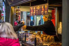 A woman selling traditional czech food `trdlo`. A woman selling czech traditional food `trdlo` or `trdelnik` in centre of Prague stock image