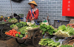 Woman is selling vegetables on the market in Stock Photos