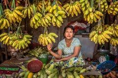 Woman sells bananas in a local market in Yangon, Myanmar Stock Photo