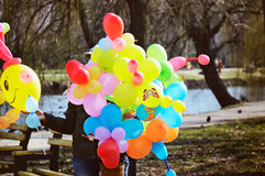 Woman sells colorful balloons in the park. tinted image Stock Image