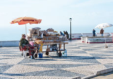 A woman sells nuts and dried fruit in old town Nazare, Portugal Royalty Free Stock Photography
