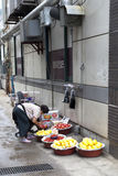 Woman sells produce on the sidewalk. Stock Images