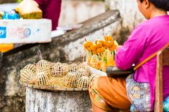 Woman sells sacrifices from the leaves of bananas and flowers, Luang Prabang, Laos. Close-up. Woman sells sacrifices from the leaves of bananas and flowers Royalty Free Stock Photography