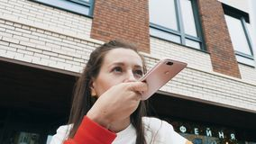 Woman send audio message with smartphone. Low angle view of young caucasian woman sending audio message on her mobile phone. Modern building at the background stock video footage