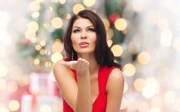 Woman sending blow kiss  over christmas lights Stock Image